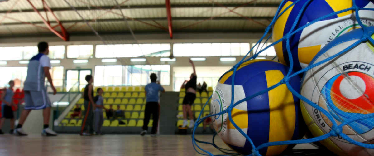 A bag of volleyballs on a court